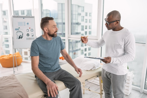 専門的な治療。彼の患者と話している間ノートを保持している快適なスマートセラピスト