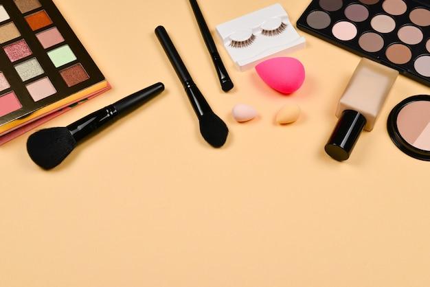 Профессиональные модные продукты для макияжа с косметическими продуктами, тональным кремом, губной помадой, тенями для век, ресницами, кистями и инструментами.