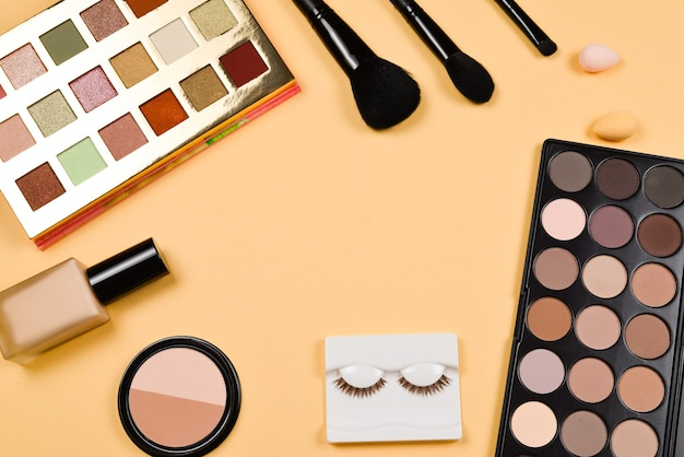 Professional trendy makeup products with cosmetic beauty products, foundation, lipstick,  eye shadows, eye lashes, brushes and tools.