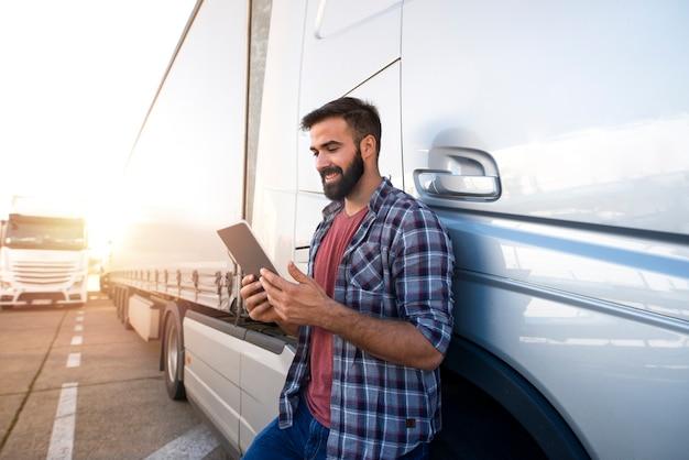 Профессиональный водитель грузовика проверяет свой маршрут на планшетном компьютере и стоит у длинного автомобиля.