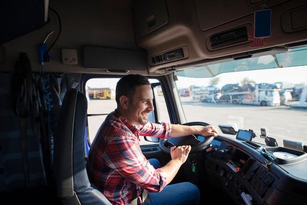 트럭을 운전하고 정시에 상품을 배달하는 미소가있는 전문 트럭 운전사