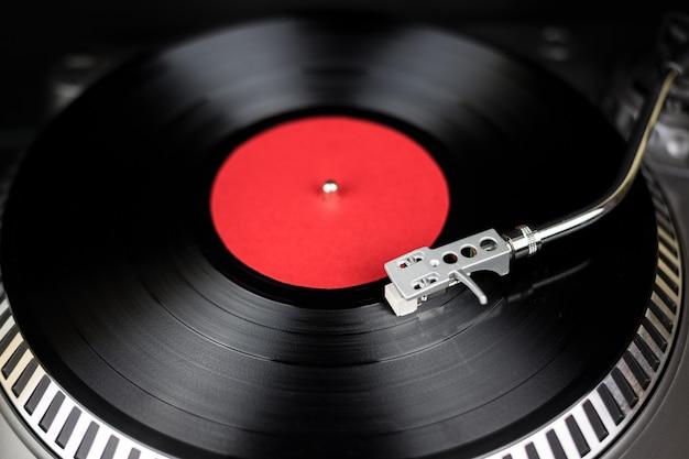 전문 턴테이블 클로즈업. 나이트 클럽에서 콘서트를위한 아날로그 무대 오디오 장비. 비닐 레코드에서 믹스 음악 트랙을 재생합니다. 턴테이블 니들 카트리지가 비닐 디스크를 긁습니다. 축제를위한 dj 설정