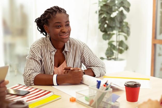 Профессиональный репетитор. радостный учитель-международник проявляет позитив во время работы в языковой школе