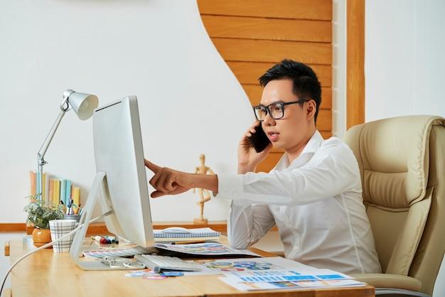 クライアントと電話で話しているプロのuiデザイナーが色の変更とフォントサイズについて顧客と話し合っています...