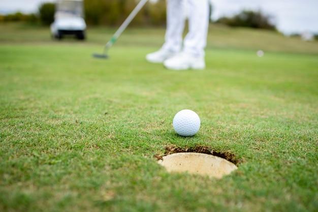 Профессиональный гольфист до неузнаваемости вводит мяч в лунку на поле для гольфа.