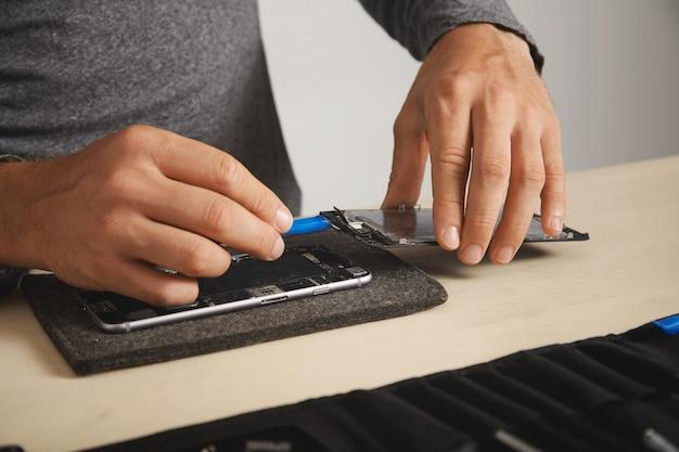 Il professionista utilizza uno strumento di apertura in plastica per scollegare i cavi dello schermo dalla scheda madre dello smartphone e rimuoverlo per sostituirlo