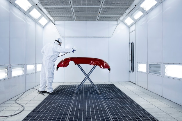 Professional vehicle painter in protective clothing painting automobile bumper with pressure gun in the chamber.