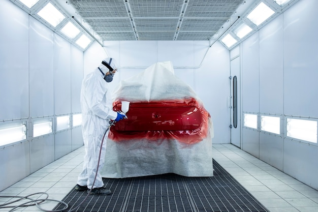Professional vehicle painter in protective clothing painting automobile with pressure gun in the chamber.