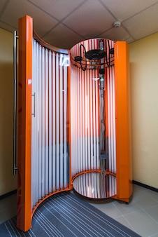 Professional vertical solarium with luminous lamps for tanning