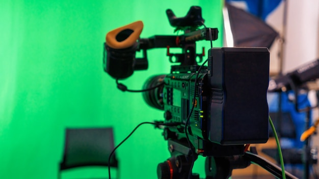 스튜디오에 녹색 크로마키가 있는 스탠드에 있는 전문 비디오 카메라