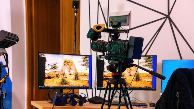スタジオのテーブルにモニターを備えたスタンド上のプロ用ビデオカメラ。仮想制作