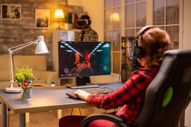 Professional video gamer female playing an online shooter game late night in the living room