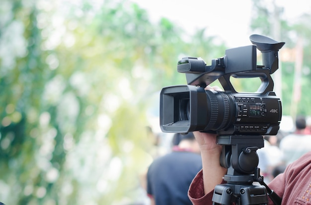 Professional video man hand holding video camera operator camcorder
