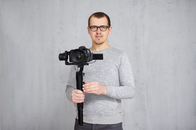 Professional videographer holding dslr camera on 3-axis gimbal over grey concrete wall with copy space