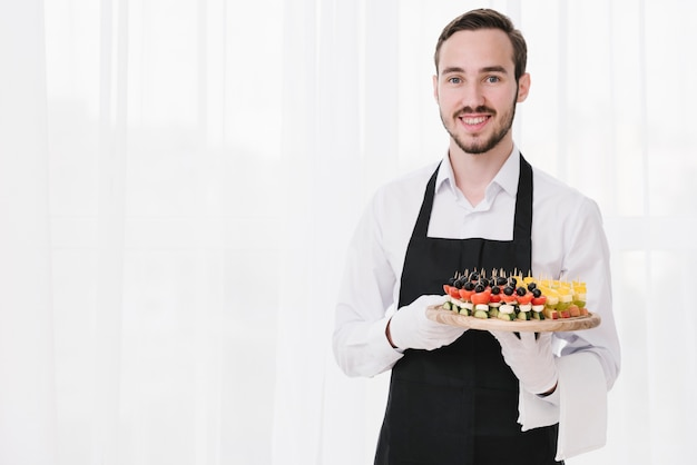 Professional waiter presenting appetizers