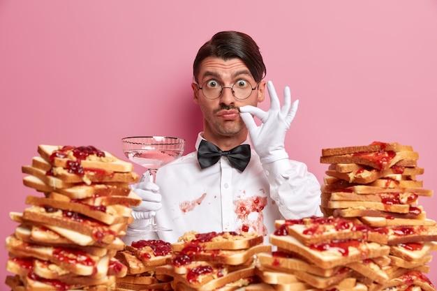 전문 웨이터가 알콜 칵테일 잔으로 서 있고, 완벽한 맛 기호를 보여주고, 분홍색 벽에 고립 된 맛있는 샌드위치를 먹은 후 잼으로 더러운 흰 셔츠를 가지고 있습니다. 서비스 및 케이터링