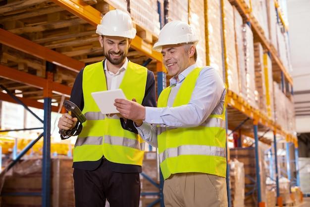 彼の部下と話をしながらタブレットを保持しているプロの倉庫マネージャー
