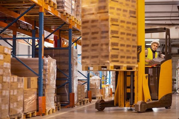 Профессиональный складской рабочий сидит в автомобиле, неся пакеты с ним