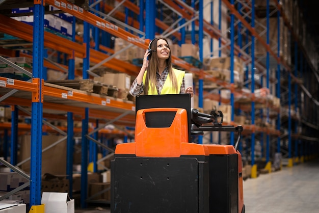 Professional warehouse worker with headset communication equipment driving forklift and relocating packages in storage center