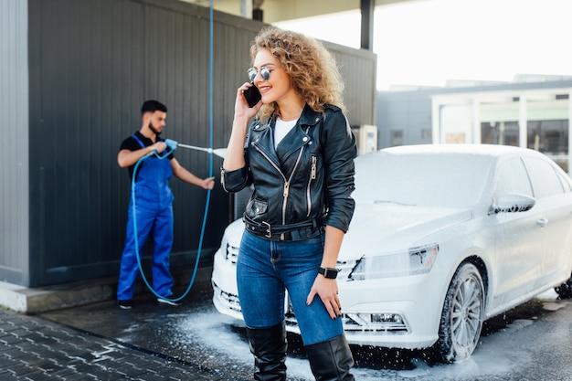 Rondella professionale in uniforme blu che lava auto di lusso con pistola ad acqua su un autolavaggio all'aperto