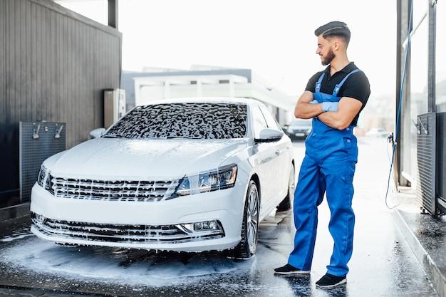 青い制服を着たプロの洗濯機高級車は泡で洗車の近くに立っています