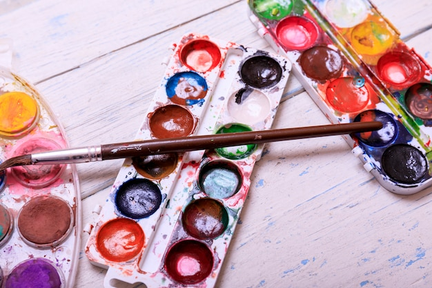 Professional watercolor aquarell paints in box with brushes on old white wooden board
