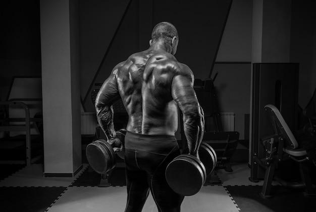 Профессиональный штангист тренируется в тренажерном зале. упражнения для спины. концепция бодибилдинга. смешанная техника