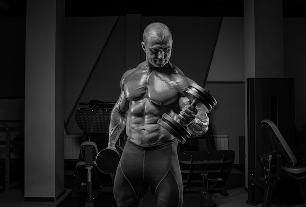 Профессиональный штангист тренируется в тренажерном зале. сгибание рук с гантелями. концепция бодибилдинга. смешанная техника
