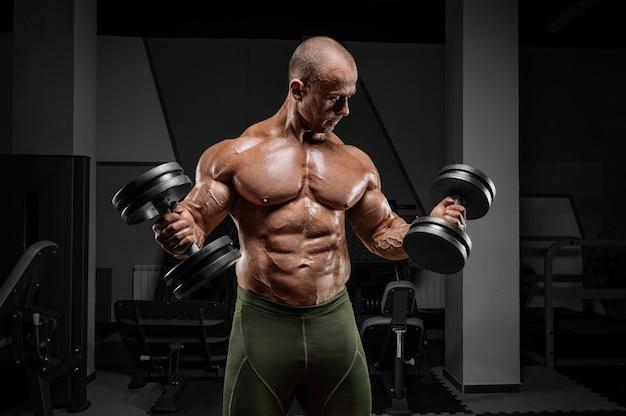 Профессиональный штангист тренируется в тренажерном зале. сгибание рук с гантелями. концепция бодибилдинга.