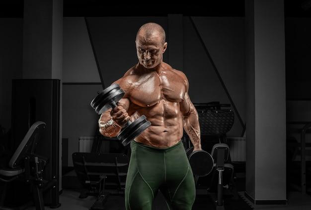 Профессиональный штангист тренируется в тренажерном зале. сгибание рук с гантелями. концепция бодибилдинга. Premium Фотографии