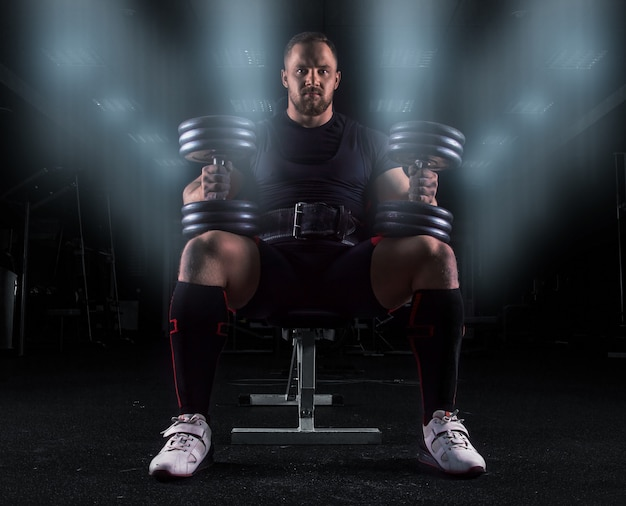 Профессиональный штангист сидит на скамейке в тренажерном зале с двумя гантелями на коленях