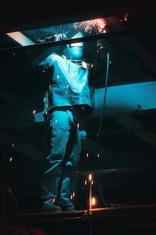 Профессиональный сварщик в защитной форме и маске сварки металлоконструкций на промышленном объекте.