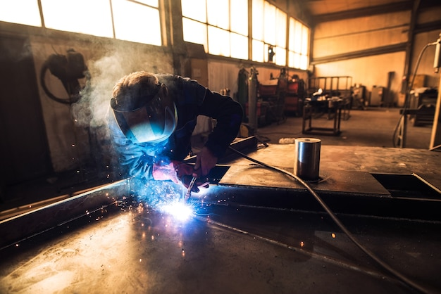 Professional welder in protective uniform and helmet welding metal part in workshop