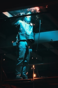 Professional welder in protective uniform and mask welding metal construction on industrial object