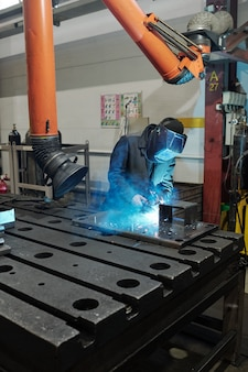 Professional welder in workwear and protective mask welding parts of huge iron industrial machine in factory workshop