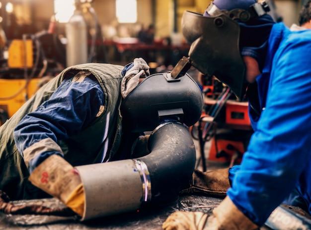 Профессиональные сварщики в защитной форме и маске сварки металлических труб в мастерской.