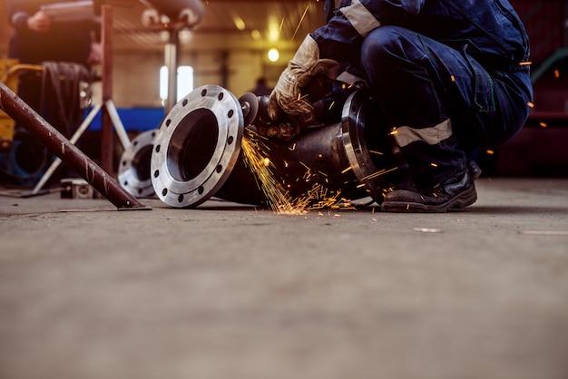 Professional welders in protective uniform and mask welding metal pipe in workshop.