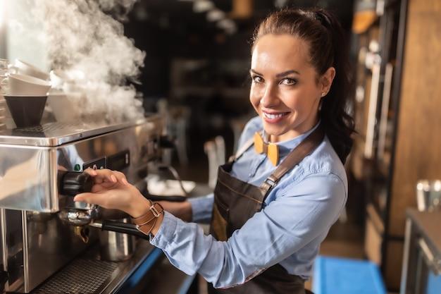 プロの身なりのよい女性バリスタがカフェのコーヒーメーカーで蒸し暑い。