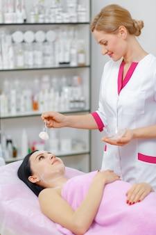 Профессиональные женщина, применение крема на лице к другой женщине