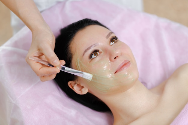 Professional woman applying green cream with a brush