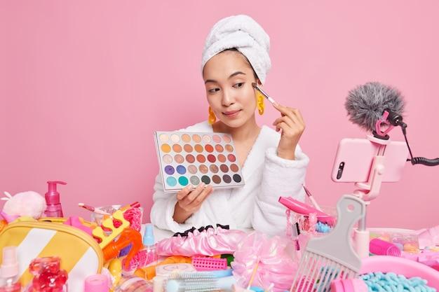 プロの女性美容ブロガーがメイクアップに関するビデオをストリーミングし、化粧ブラシでカラフルな影を適用し、パレットレコードをオンライン美容コースで保持します