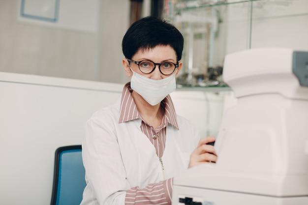 Профессиональная женщина-врач, использующая для проверки зрения электронного цифрового современного оборудования, проверки зрения