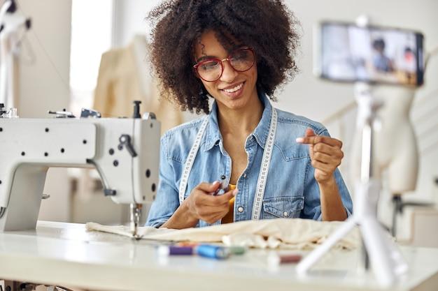 プロの女性ファッションデザイナーが現代のミシンで働くブログの新しいビデオを撮影します
