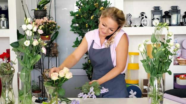プロの女性花屋さんがスマホで注文して話し、フラワーショップで花束を作ってくれます。美しい束を作成するフローリストリースタジオのエプロンで成熟した女性。自営業者の概念。