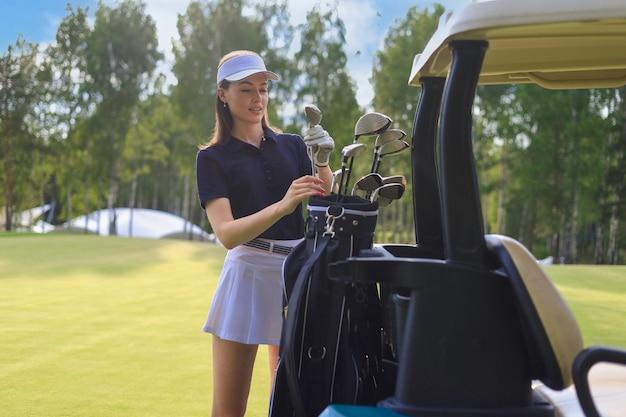 バッグからゴルフクラブを選ぶプロの女性ゴルフプレーヤー。