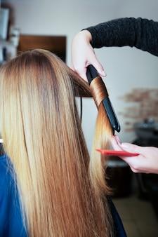 Профессиональный парикмахер женщина делает прическу с помощью щипцов для завивки для длинных волос молодой женщины в салоне красоты.