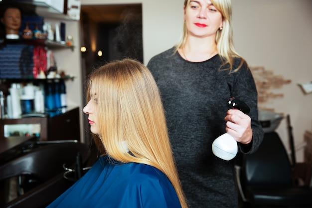 전문 여성 미용사는 미용실에서 머리카락에 스프레이를 사용합니다.