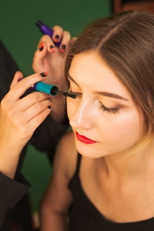 Professional woman making up girl's eyes