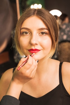 Professional woman making up girl's lips
