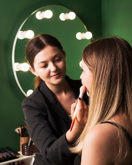 Professional woman making up girl
